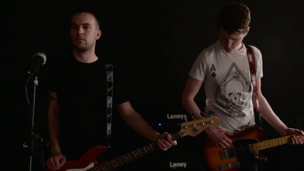 Two guitarists stood against a black backround. One of them is stood by a microphone. Both are waiting to begin playing.